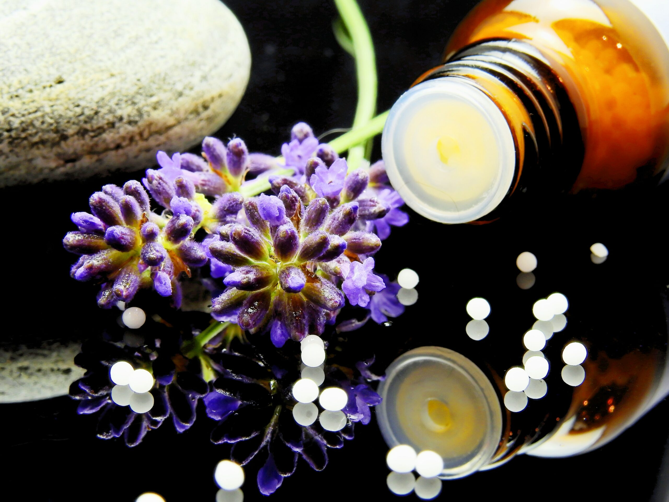 Purple flowers next to bottle of homeopathic medicine